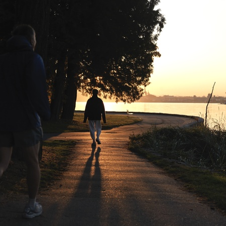 People walking on the sea wall at dusk in Vancouver, British Columbia, Canada
