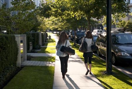 sidewalks: Two women walking on a sidewalk in Vancouver, British Columbia, Canada