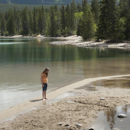 edith: Girl sitting at the lakeside, Edith Lake, Jasper National Park, Alberta, Canada Stock Photo
