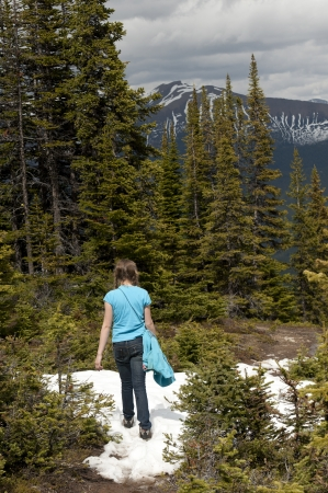 getting away from it all: Rear view of a girl walking on snow covered trail, Bald Hills, Jasper National Park, Alberta, Canada