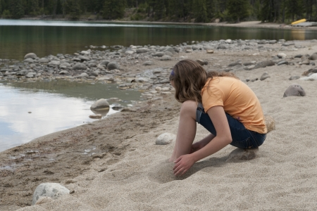 edith: Girl playing with sand at the lakeside, Edith Lake, Jasper National Park, Alberta, Canada