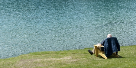 canadian rockies: Senior man sitting on a chair at the lakeside, Beauvert Lake, Jasper National Park, Alberta, Canada
