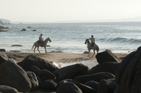 Tourists riding horses on the beach, Sayulita, Nayarit, Mexico photo
