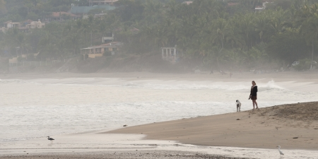 cliff edge: Woman standing on the beach with a dog, Sayulita, Nayarit, Mexico