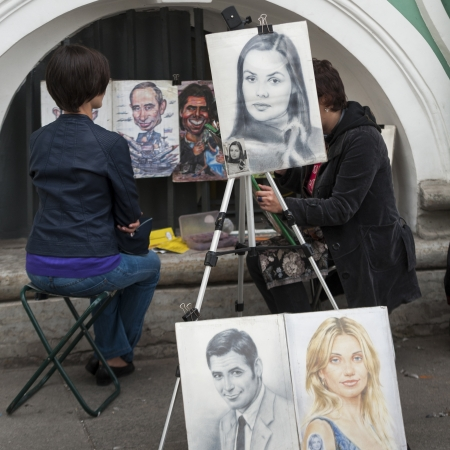 Artist drawing portrait of a woman in a street, Palace Square, St. Petersburg, Russia