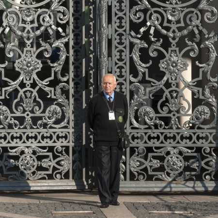 Security officer standing in front of a gate of Winter Palace at State Hermitage Museum, Palace Square, St. Petersburg, Russia