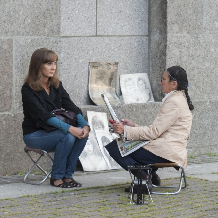 Female artist drawing a portrait of a woman on a street, Palace Square, St. Petersburg, Russia
