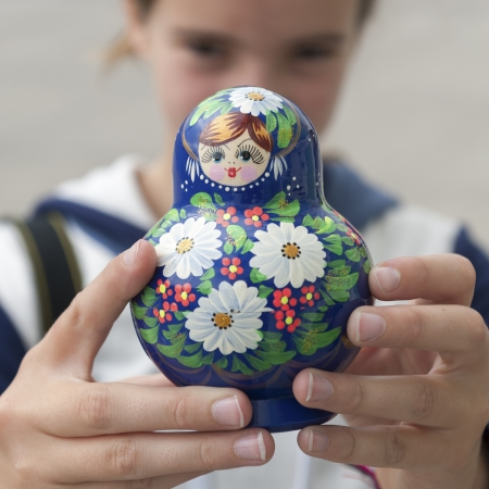 traditionally russian: Close-up of a girl showing a Russian nesting doll, St. Petersburg, Russia