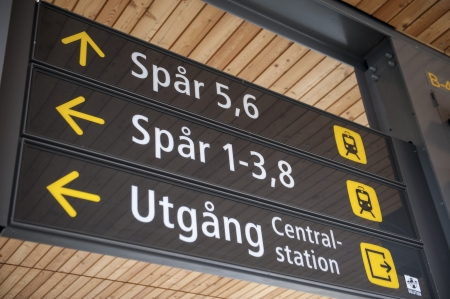western script: Low angle view of directional signs at a station, Uppsala, Sweden Editorial