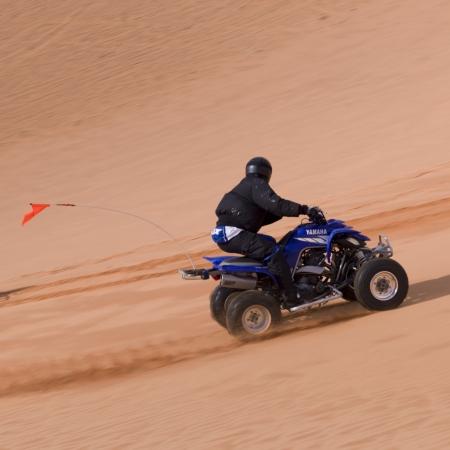 quad: Man riding a quad bike in a desert, Coral Pink Sand Dunes State Park, Utah, USA