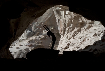 Woman exercising in Ulrike's Cave, Amangiri, Canyon Point, Utah, USA photo