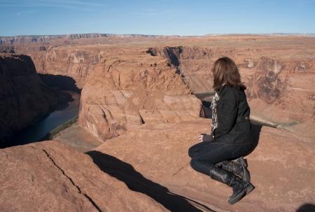 Woman sitting on a rock looking at a view, Horseshoe Bend, Glen Canyon National Recreation Area, Arizona-Utah, USA