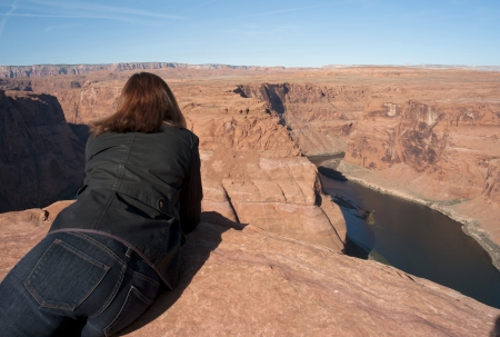 Woman leaning on rock looking at a view, Horseshoe Bend, Glen Canyon National Recreation Area, Arizona-Utah, USA