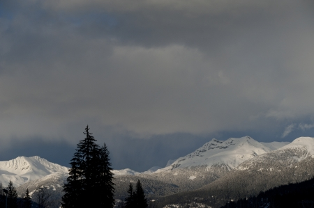 Clouds over snow covered mountains, Whistler, British Columbia, Canada photo
