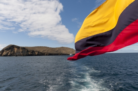 Ecuadorean flag with an island in the background, Isabela Island, Galapagos Islands, Ecuador photo