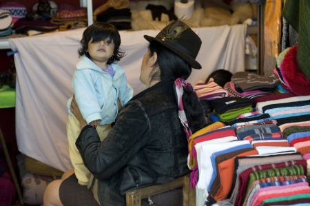 Woman with her daughter sitting in a clothing store, Quito, Ecuador