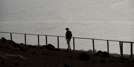 Tourist walking on a volcanic area, Bartolome island, Galapagos Islands, Ecuador photo