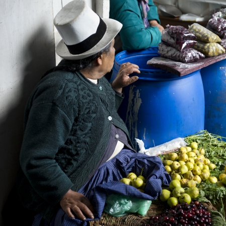 economic theory: Vendor selling fruits at a market stall, Mercado Central, Cuzco, Peru Editorial