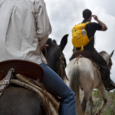 packsack: Tourists riding on horses, Sacred Valley, Cusco Region, Peru Stock Photo