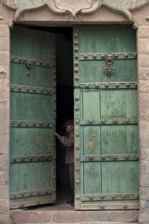 Man opening the door of a building, Plaza De Las Nazarenas, Cuzco, Peru Stock Photo