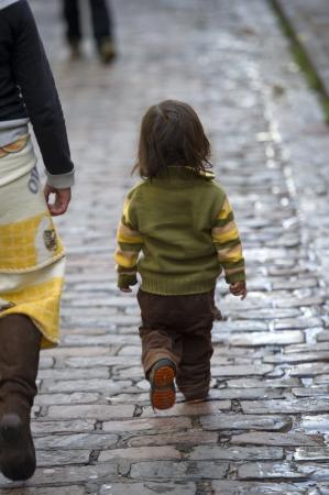 peruvian ethnicity: Ni�o caminando con su madre en una calzada empedrada, Cusco, Per� Foto de archivo