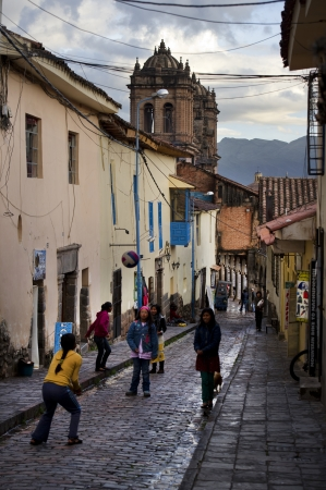 Children playing volleyball on a wet street, Cuzco, Peru Stock Photo - 16769043