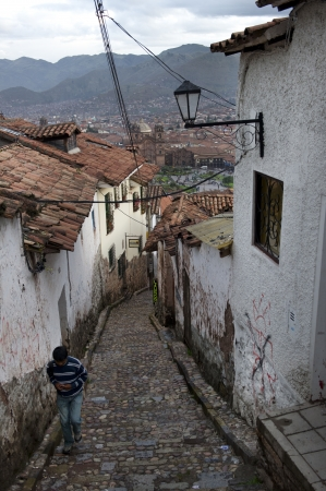 cusco province: Person moving up in a stepped alley in Cuzco, Peru
