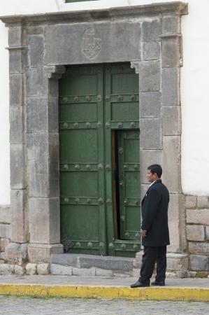 peruvian ethnicity: El hombre de pie delante de una puerta en la Plaza de las Nazarenas, Cusco, Per�