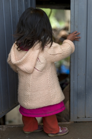 cusco region: Small girl standing at a doorway, Sacred Valley, Cusco Region, Peru Editorial