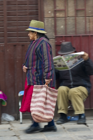 peruvian ethnicity: Woman carrying a bag and walking in a street, Sacred Valley, Cusco Region, Peru