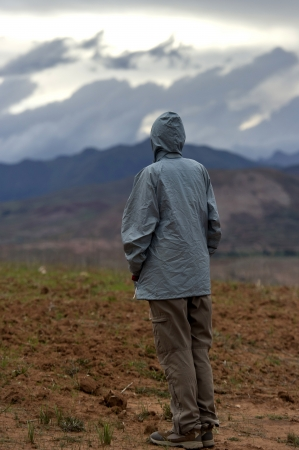 free time: Rear view of a man standing in the field, Sacred Valley, Cusco Region, Peru Stock Photo