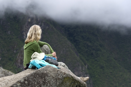 Woman sitting on a stone at The Lost City of The Incas, Machu Picchu, Cusco Region, Peru