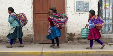 bundles: Women carrying bundles walking on a sidewalk, Pisac, Sacred Valley, Cusco Region, Peru