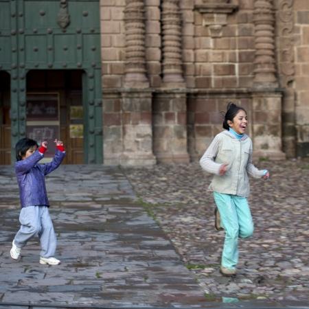 peruvian ethnicity: Muchacho que juega con su hermana en un mercado, la Plaza de Armas, Cusco, Per�