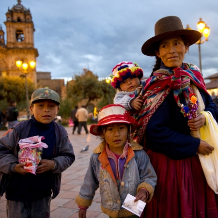 ni�os latinos: Mujer con sus hijos en una plaza con Iglesia de la Compa��a en el fondo, la Plaza de Armas, Cusco, Per� Foto de archivo