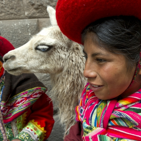 Close-up of a girl with a llama (Lama glama), Cuzco, Peru