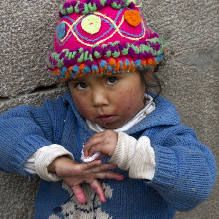 cuzco: Portrait of a girl cleaning her fingers, Cuzco, Peru