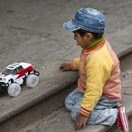 peruvian ethnicity: Ni�o jugando con un coche de juguete, Cusco, Per�