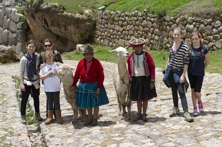 full disclosure: Tourists and a Peruvian woman standing with a llama and alpaca, Sacsayhuaman, Cuzco, Peru