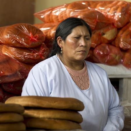 peruvian ethnicity: Vendedora de pan en el Mercado Central, Cuzco, Per� Foto de archivo