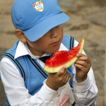 Boy eating watermelon at Mercado Central, Cuzco, Peru