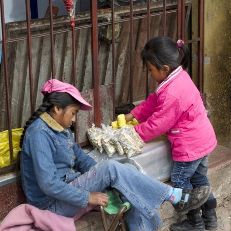 niños latinos: Dos chicas en un puesto del mercado, Valle Sagrado, Cusco, Perú