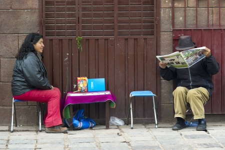 Man reading a newspaper at a market stall with a woman sitting beside him, Sacred Valley, Cusco Region, Peru