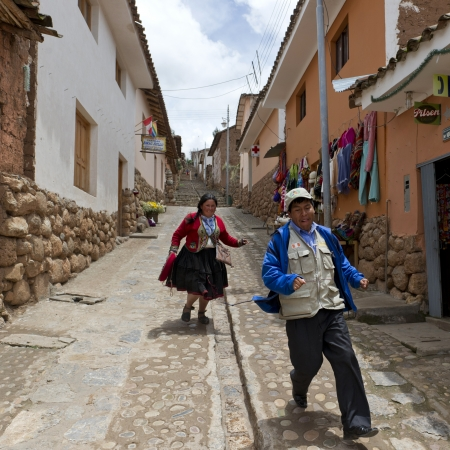 Man and woman running in a street, Sacred Valley, Cusco Region, Peru