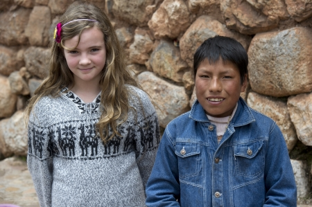 Two friends standing in front of a stone wall, Sacred Valley, Cusco Region, Peru Stock Photo - 17227935