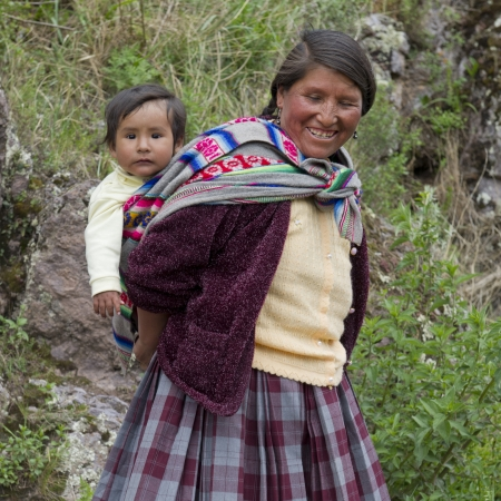 cusco region: Woman carrying her son on back and smiling, Pisac, Sacred Valley, Cusco Region, Peru