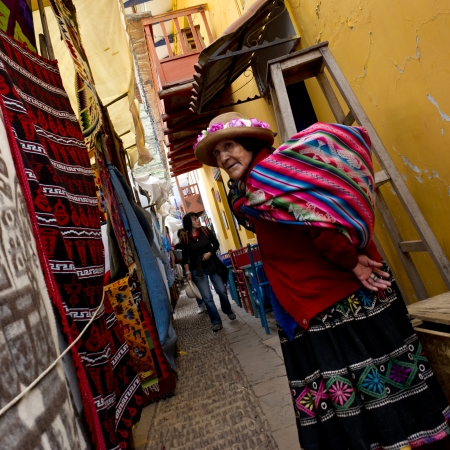 tradition: Woman standing at Sunday market, Pisac, Cuzco, Peru Editorial