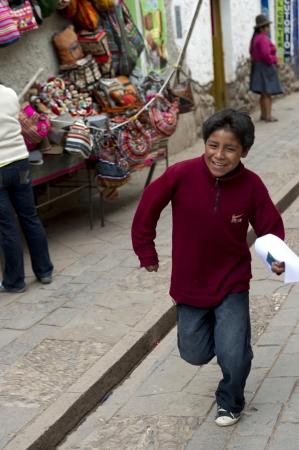 satisfies: Boy running at Sunday market, Pisac, Cuzco, Peru