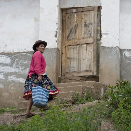 sacred valley of the incas: Quechua Indian woman walking towards the entrance of Chumpepoke Primary School, Poques, Sacred Valley, Cusco Region, Peru Editorial