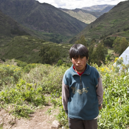 Quechua Indian boy standing with valley in the background, Chumpepoke Primary School, Poques, Sacred Valley, Cusco Region, Peru